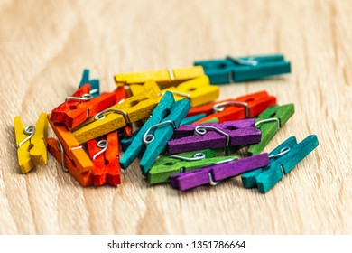 Colorful laundry clips disorganized on vintage wood background. Vintage background. Lots of colored pegs. Many different colored clothes pegs close up. Lots of clothespins.