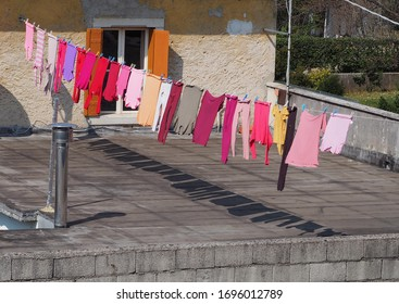Colorful laundry hanging to dry on a clothesline in a terrace. The clothes colors are mostly pink purple and red.