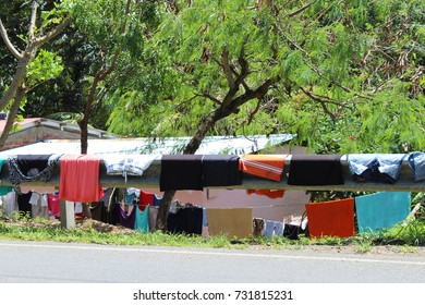 Colorful laundry hanging to dry on a metal guardrail in San Juan Del Sur, Nicaragua.