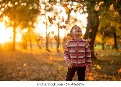 Colorful leaves falling down in autumn season, girl child enjoying in the park.