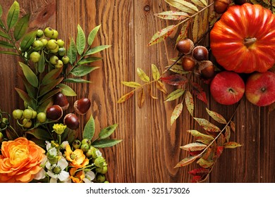 colorful leaves, fruits and flowers on wooden background