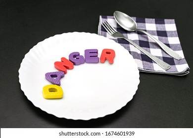 Colorful letters with word danger on plate with fork and knife, food additive and unhealthy food concept