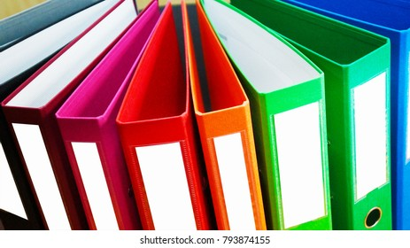 Colorful lever arch file folders in one line. Thick document cases of different colors with white fields for text and iron rings in the cover. Office stationery for background