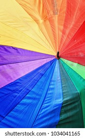 Colorful LGBT rainbow umbrella belonging to an old Ifugao woman wide open and leaning on the sidewalk of the bus station in Sagada town. Mountain province-Cordillera region-Luzon island-Philippines.