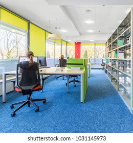 Colorful library interior with computer workstation and modern shelving