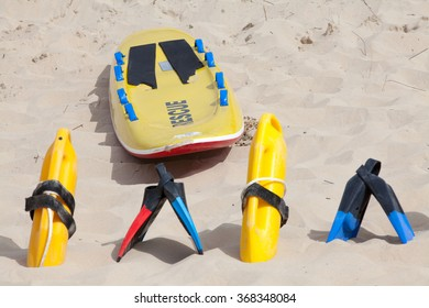 Colorful lifesaving equipment lying on the beach sand in the hot summer sun