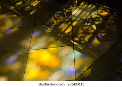 Colorful light spots on the tiled floor in the church and shadow of forging fence. Sunlight filtered through the stained glass window.