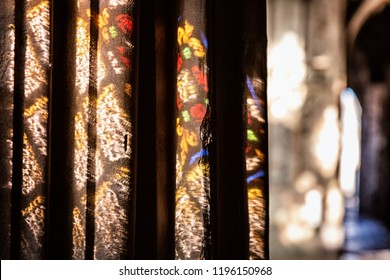 Colorful light spots on the wall in the church . Sunlight filtered through the stained glass window. Ancient historical cathedral in england UK