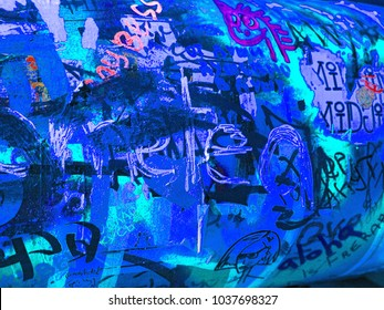 Colorful light steel blue, dark orchid and slate blue sprayed graffiti on aged cracked brick wall with drips, smears and peeling paint. Street art.