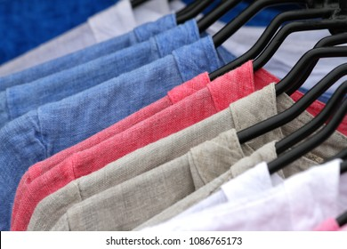Colorful linen shirts hanging in a closet close up detail