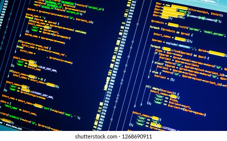 Colorful lines of php code on the monitor on blue background, close up