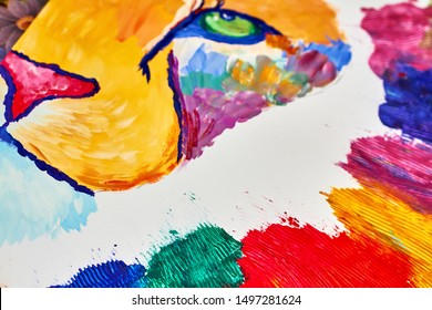A colorful lion on canvas drawn by a child using a brush and knife. Closeup, selective focus