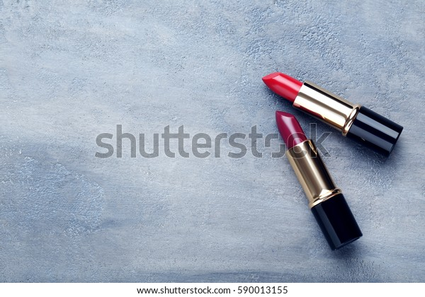 グレイの木のテーブルの上にカラフルな口紅