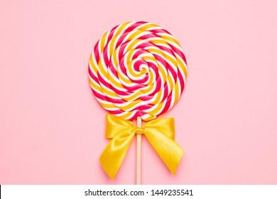 Colorful lolipop with wooden stick, pink, yellow and white spiral on pink background , childhood sweets