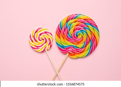 Colorful lolipops spiral with wooden stick on pink background , childhood sweets