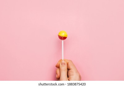 Colorful lollipop candy cane in hand. Strawberry banana sweetness on pink background.