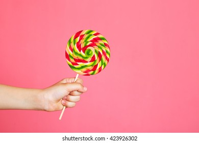 Colorful lollipop in child hand on pink background. Copy space.