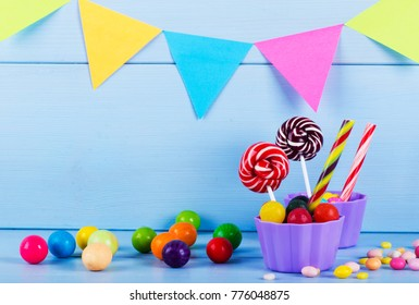 Colorful lollipops, candy canes and sweet candies mix on wooden background