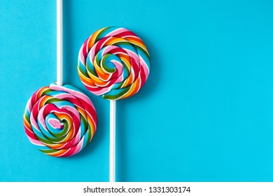 Colorful lollipops on blue background. Copyspace