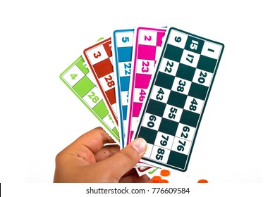 Colorful lotto or bingo game papers with numbers on hand, isolated on white background.