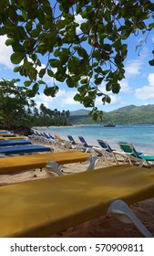 Colorful lounge chairs in the foreground with blue water and palm trees in the background at Playa Rincon, a beach in the Dominican Republic