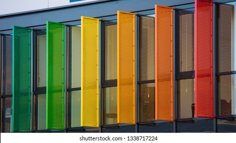 Colorful louvers background. Different rainbow color windows facade pattern of a modern building. Abstract blinds design and architecture concept. Office shutters exterior texture close up fragment.