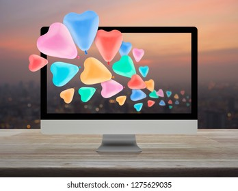 Colorful love heart balloon with desktop modern computer on wooden table over blur of cityscape on warm light sundown, Business internet dating online, Valentines day concept