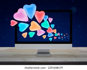 Colorful love heart balloon with desktop modern computer on wooden table over fantasy night sky and moon, Business internet dating online, Valentines day concept