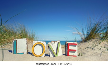 colorful love letters in the sand dunes at the ocean