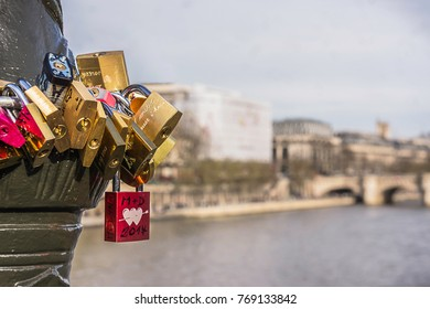 Colorful love locks in Paris on the Arts Bridge with a soft and clear background.