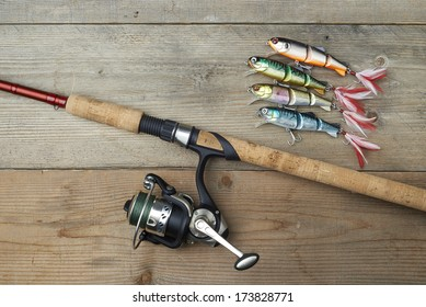 lot of colorful lures with the fishing rod on the wooden pier