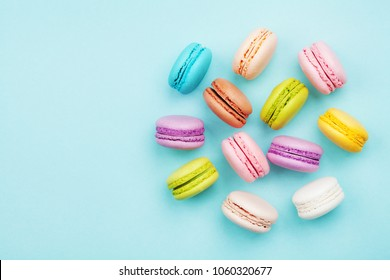 Colorful macaron or macaroon on blue pastel background from above. Fashion dessert top view.