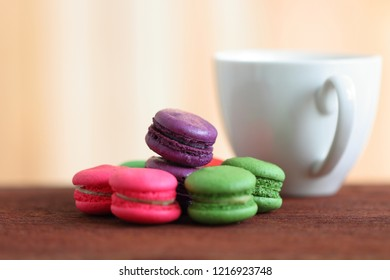 Colorful Macaron with a white mug of hot coffee on wooden floor, copy space.