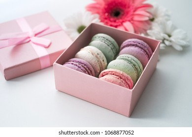 colorful macarons in a box on white with flowers