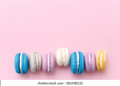 Colorful macarons cake, top view flat lay, sweet macaroon on color pink isolated background. Minimal concepts pattern above, food background