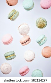 Colorful macarons cake, top view flat lay, fly falling sweet macaroon on color pink isolated background. Minimal concepts falling macaroons pattern above, food natural background