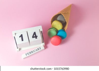 Colorful macarons in ice cream cone with wooden calendar. Valentine's day concept.