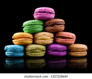 Colorful macarons isolated on black background. Sweet french macaroons assortment pyramid heap.