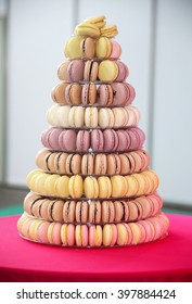 Colorful macarons on pyramid-shaped plastic stand on many visible levels