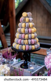 Colorful macarons on pyramid-shaped plastic tower stand as part of candy bar sweet table