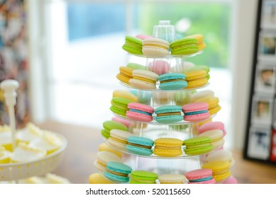 Colorful macarons on pyramid-shaped plastic stand at wedding party