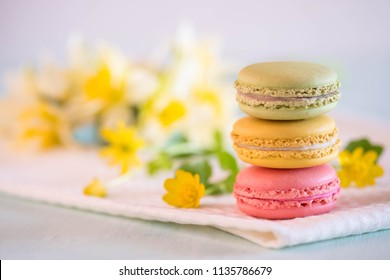 Colorful macarons on towel with yellow flowers and narcissus