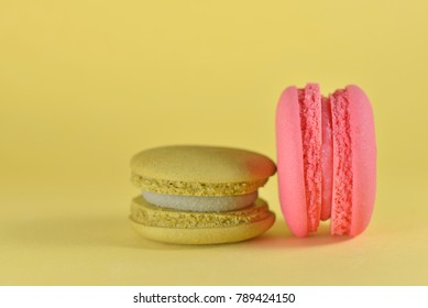 Colorful macarons on yellow background. Colorful creative concept with copy space for design works. Sweet dessert for relaxing time. Idea for wallpaper and beautiful greeting card. Minimal concept