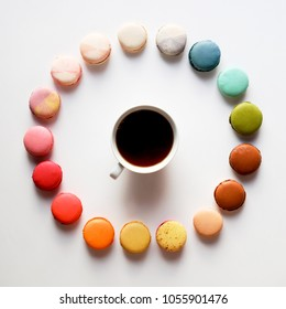 Colorful macaroons with cup of tea, circle rainbow colora macarons