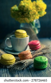 Colorful macaroons and first spring flowers on old wooden background