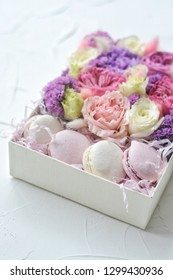 Colorful macaroons and flowers on table. Sweet macarons in gift box.