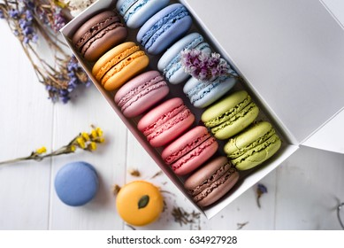 Colorful macaroons and flowers on wooden table. Sweet macarons in gift box. Flat lay