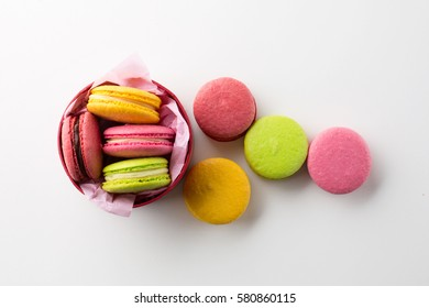 Colorful macaroons gift box. Sweet macarons present on white background with copy space. Top view. Holiday time concept