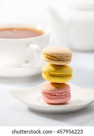 Colorful macaroons on a plate on background tea set