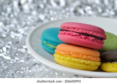 Colorful macaroons are on a plate with foil background.